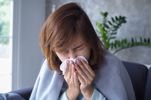 As mulheres asiáticas têm corrimento nasal e pegam um resfriado, tosse, espirros, febre, sentadas doentes no sofá dentro de casa. Foto Premium