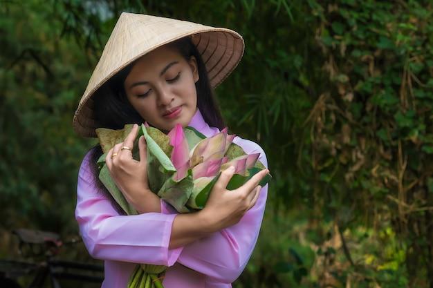 As mulheres asiáticas tradicionais vietnam são bicicleta do trole da menina à loja após a cesta da flor de lótus. Foto Premium