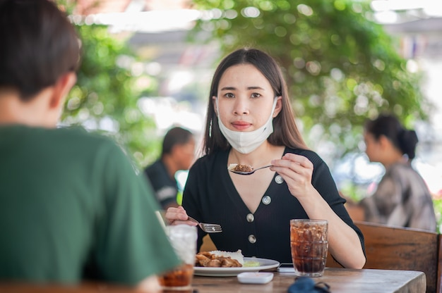 As mulheres asiáticas usam máscara facial sentado no restaurante foco suave, novo conceito normal Foto Premium