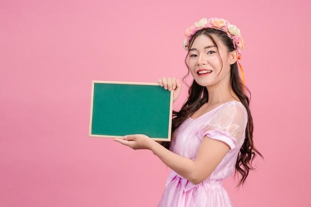 As mulheres bonitas, vestidas com vestidos de princesa rosa, prendem uma placa verde em um rosa. Foto gratuita
