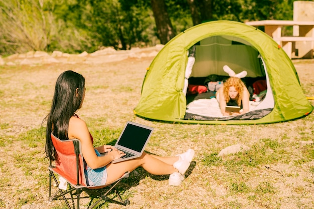 As mulheres com gadgets passam o tempo ao ar livre Foto gratuita