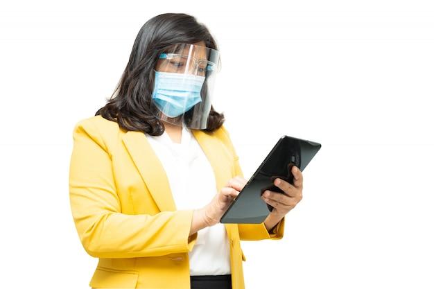 As mulheres de negócio asiáticas usam a máscara vestindo da tabuleta e o protetor de cara no fundo branco. Foto Premium