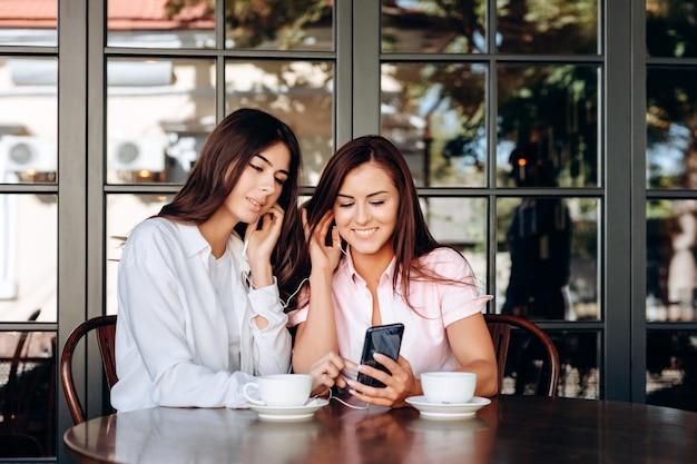 As mulheres de negócios sorridentes estão ouvindo falhas importantes nos fones de ouvido. Foto Premium