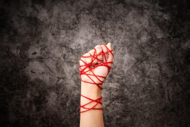 As mulheres entregam amarrado com corda, a ideia da expressão da liberdade no fundo escuro do grunge na baixa chave. Foto Premium