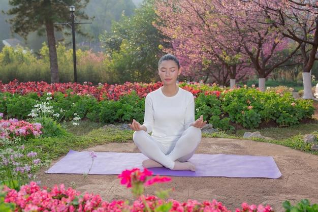 As mulheres estão jogando yoga no parque Foto gratuita
