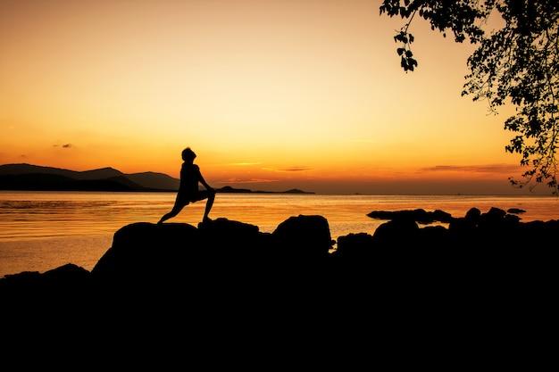As mulheres exercem e relaxam no fundo do sol da praia Foto Premium