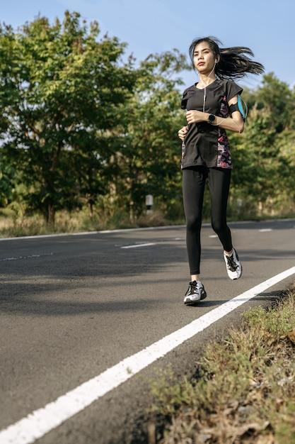 As mulheres exercitam correndo na estrada. Foto gratuita