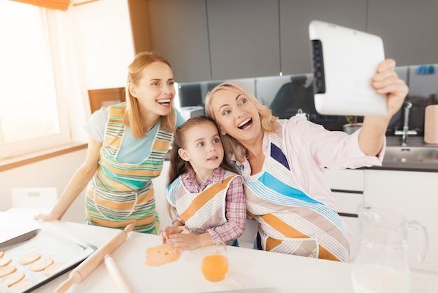 As mulheres fazem selfies com uma garota na cozinha. Foto Premium