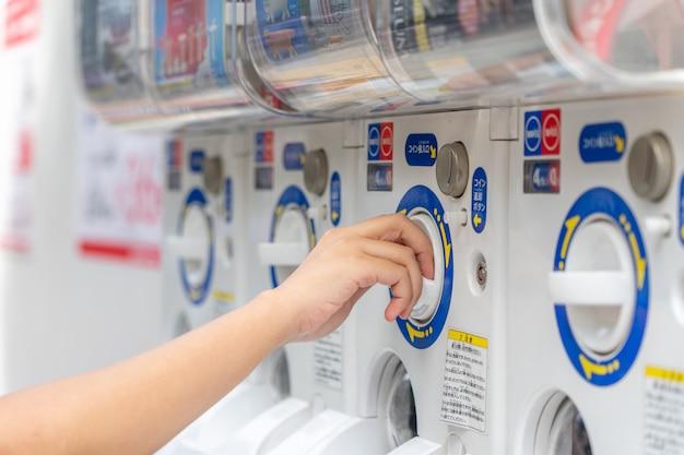 As mulheres inserem moedas na máquina da cápsula Foto Premium