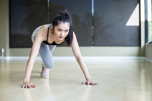 As mulheres jovens se aquecem antes de se exercitarem empurrando o chão e dobrando os joelhos no ginásio. Foto gratuita