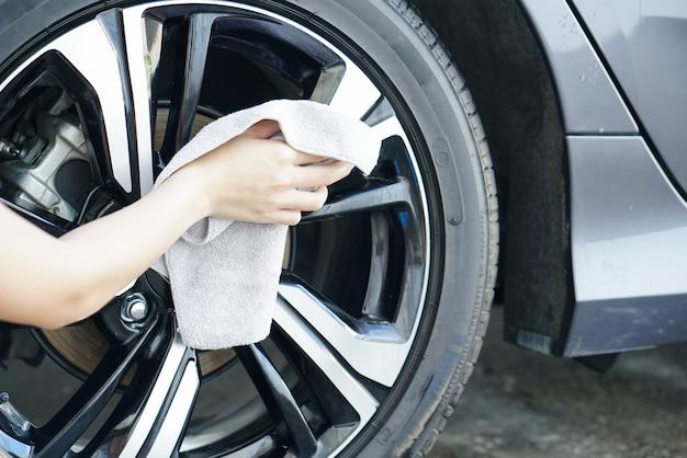 As mulheres mão seca limpando a superfície do carro com pano de microfibra após a lavagem. Foto Premium
