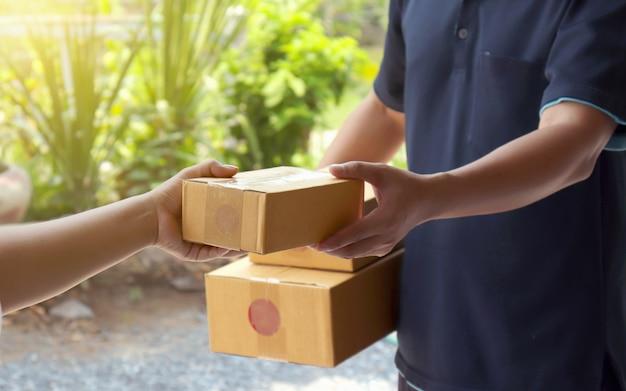 As mulheres receberão pacotes do pessoal de entrega profissional em segundo plano, desfocado Foto Premium