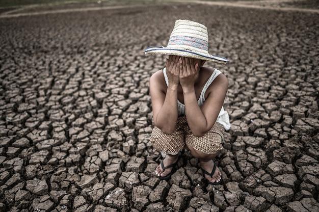 As mulheres sentadas em suas mãos fecharam os rostos em solo seco em um mundo em aquecimento. Foto gratuita