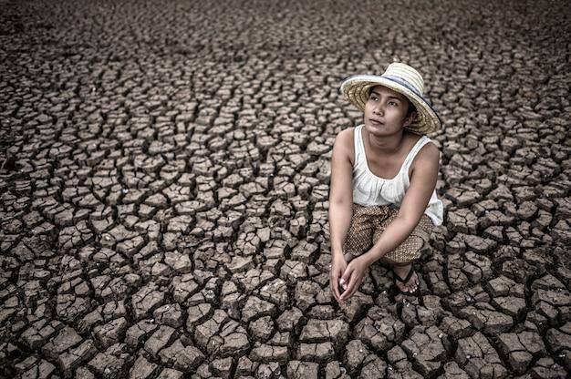 As mulheres sentam-se olhando o céu em clima seco e aquecimento global. Foto gratuita