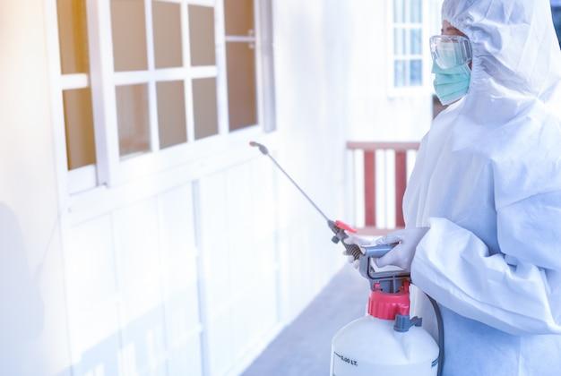 As mulheres usam roupas de proteção pessoal, óculos, máscaras e luvas, fazendo desinfecção e descontaminação em um local público para reduzir a propagação de doenças durante a crise covid-19. Foto Premium