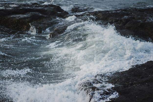 As ondas do oceano estão quebrando contra as rochas. espirrando ondas do mar ao pôr do sol. Foto gratuita