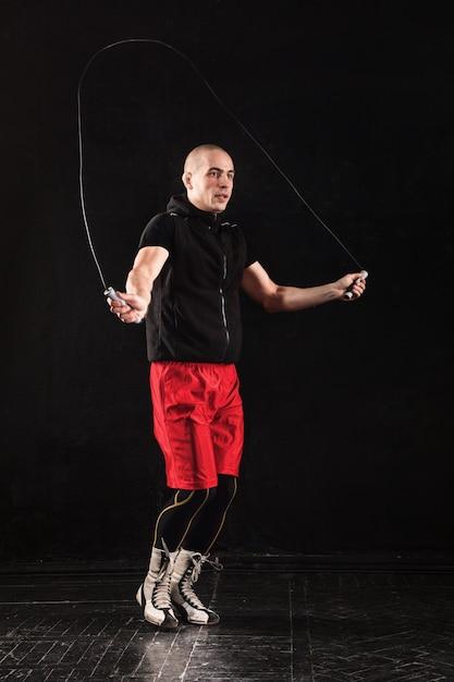 As pernas de um homem musculoso com treinamento de kickboxing corda para pular no preto Foto gratuita