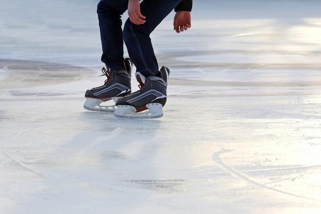 As pernas de um homem patinando na pista de gelo Foto Premium
