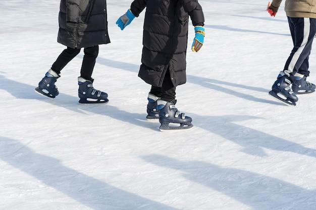 As pessoas andam na pista de patinação na pista de gelo durante as férias de natal. Foto Premium