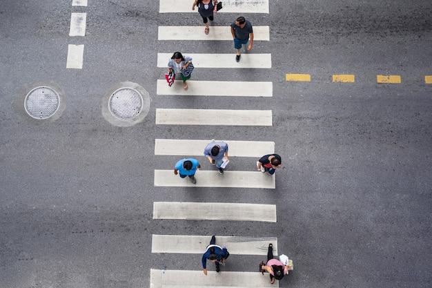 As pessoas andam na rua na cidade ao longo da estrada de tráfego de passagem para pedestres Foto Premium