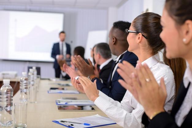 As pessoas aplaudem o orador na reunião de negócios Foto Premium