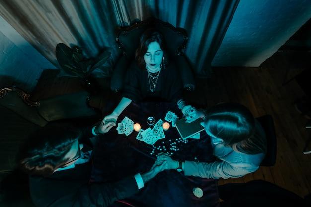 As pessoas dão as mãos da noite na mesa com velas Foto gratuita