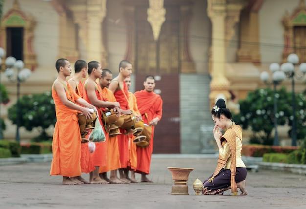 As pessoas dão oferendas de comida aos monges budistas em vientiane, laos. Foto Premium
