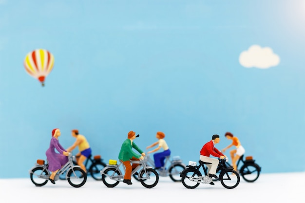 As pessoas em miniatura gostam de andar de bicicleta em fundo azul. Foto Premium