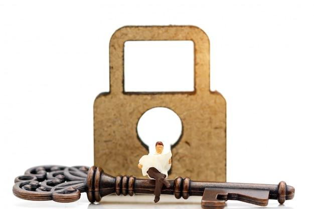 As pessoas em miniatura leem o livro para descobrir como desbloquear a chave. Foto Premium