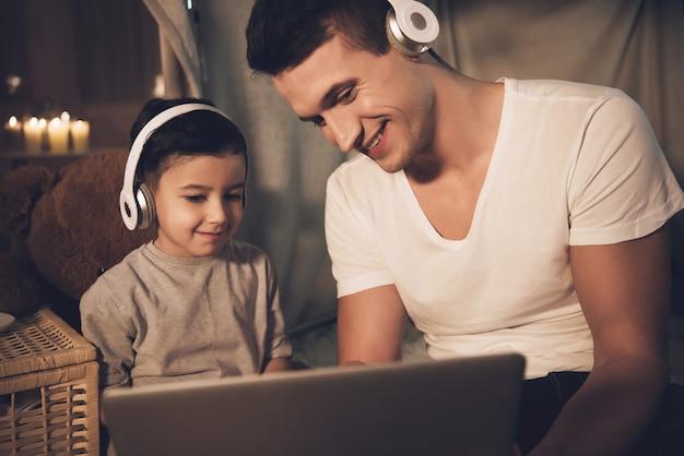 As pessoas estão assistindo filme no laptop em fones de ouvido à noite. Foto Premium