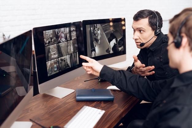 As pessoas estão sentadas em frente aos monitores na sala de segurança Foto Premium
