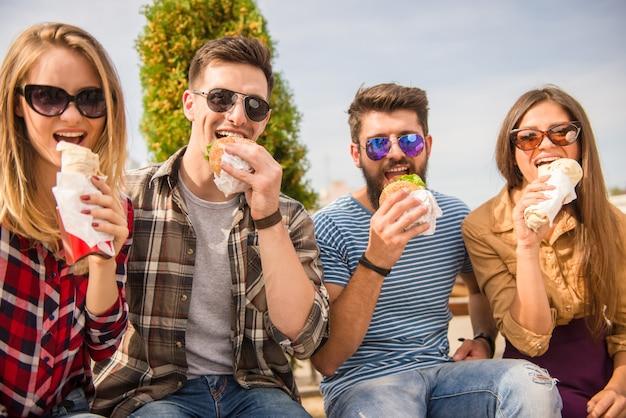 As pessoas estão sentadas no parque e comendo comida. Foto Premium
