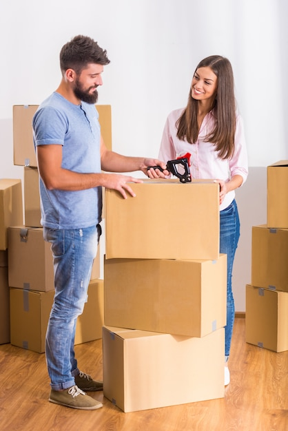As pessoas ficam perto de caixas e desempacotam caixas. Foto Premium
