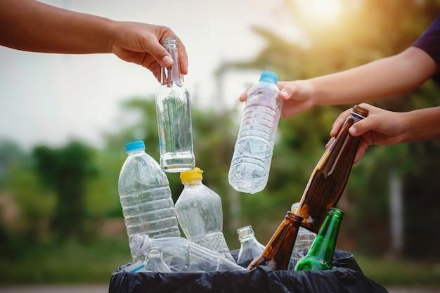 As pessoas mão segurando a garrafa de lixo de plástico e vidro, colocando em saco de reciclagem para limpeza Foto Premium