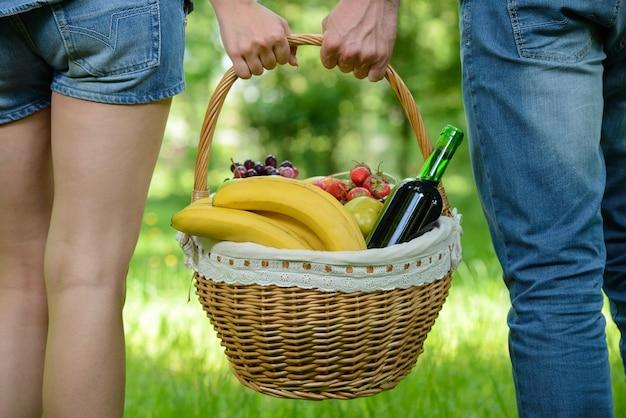 As pessoas são andar no piquenique no parque, segurando uma cesta de comida. Foto Premium