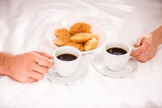 As pessoas sentam-se em casa e bebem café com croissants. Foto Premium