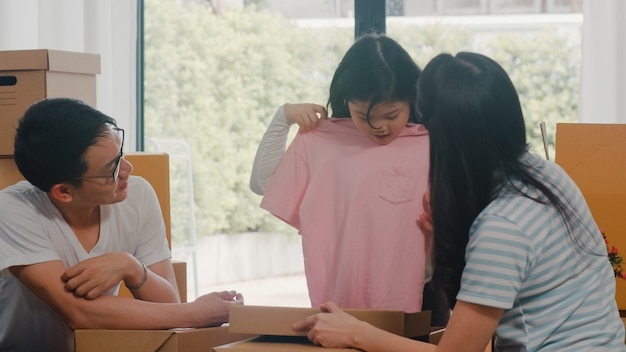 As remoções novas asiáticas felizes do internamento da família estabelecem-se na casa nova. pais coreanos animados descompactam caixas de papelão junto com a filha segurando a roupa na sala de estar em casa no dia da mudança. Foto gratuita