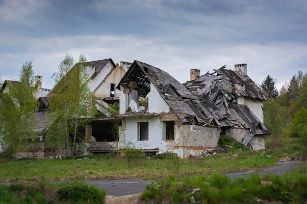 As ruínas de uma antiga casa de tijolo com um telhado de madeira e árvores Foto Premium