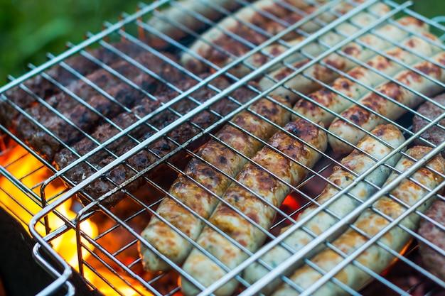 As salsichas de carne de porco cruas roasted na grade, assam a estação fora. carne assando no churrasco. Foto Premium