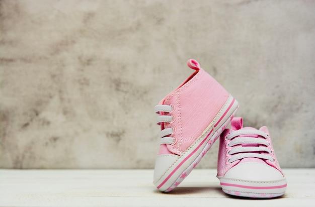 As sapatilhas cor-de-rosa do bebê, sapatas do esporte fecham-se acima de newbord, maternidade, conceito da gravidez com espaço da cópia. Foto Premium