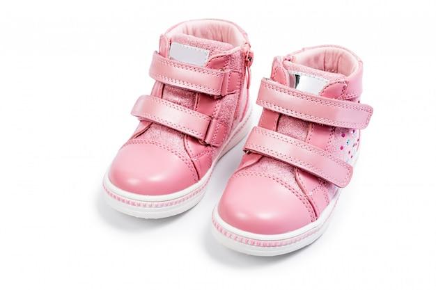 As sapatilhas das crianças-de-rosa isoladas em um branco Foto Premium