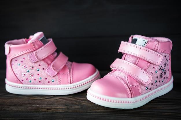 As sapatilhas das crianças-de-rosa isoladas em um fundo preto de madeira Foto Premium