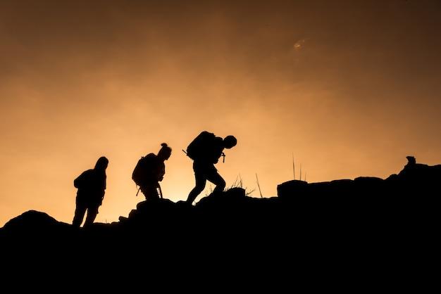 As silhuetas do grupo de caminhantes estão indo para o cume Foto Premium