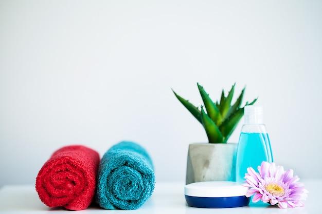 As toalhas e o gel gelam na tabela branca com espaço da cópia no fundo da sala do banho. Foto Premium