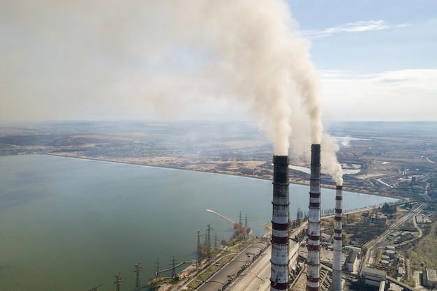 As tubulações altas da usina, o fumo branco na paisagem rural, a água do lago e o céu azul copiam o espaço. Foto Premium