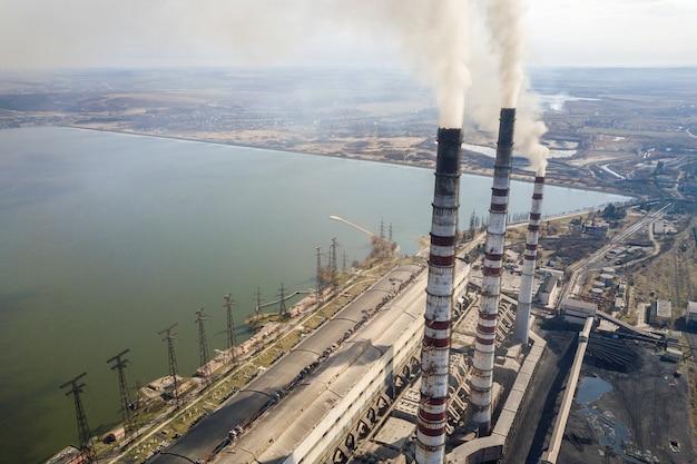 As tubulações altas da usina, o fumo branco na paisagem rural, a água do lago e o céu azul copiam o fundo do espaço. Foto Premium