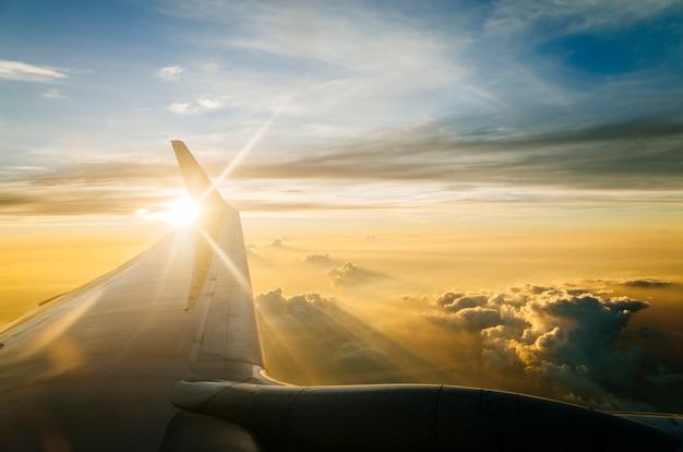 Asa de avião no céu azul no crepúsculo e pôr do sol Foto gratuita