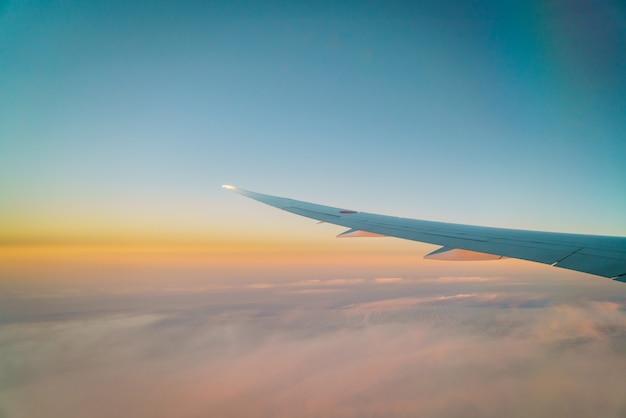 Asa de um avião voando acima das nuvens Foto gratuita