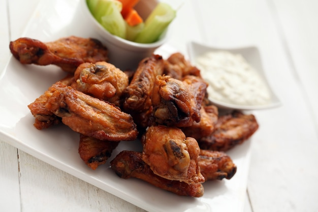 Asas de frango com molho e legumes Foto gratuita