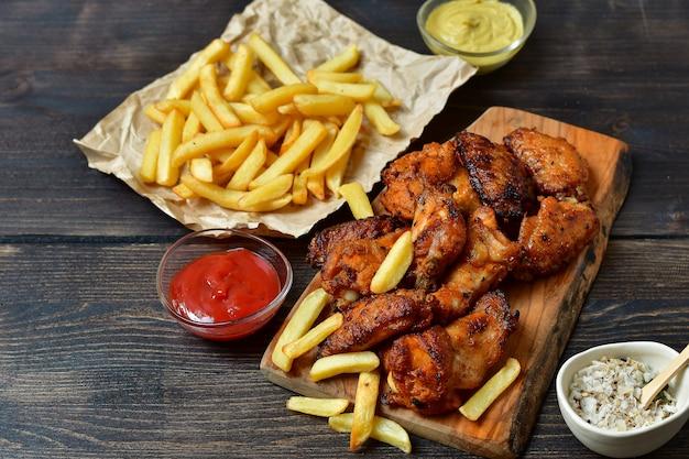 Asas de frango e batatas fritas com ketchup e mostarda. Foto Premium